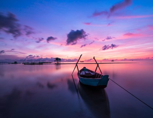 barque au milieu de l'eau et couché de soleil