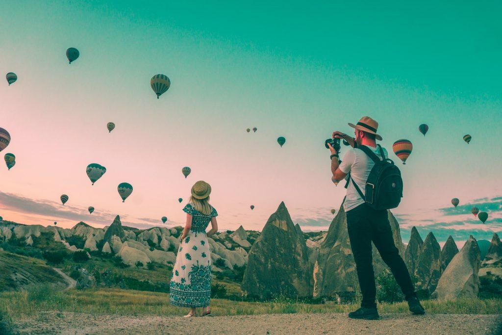 homme et femme prenant en photo des montgolfières