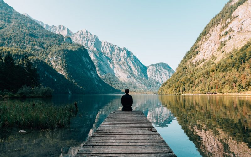 homme au bord d'un ponton avec vue sur un lac et montagne