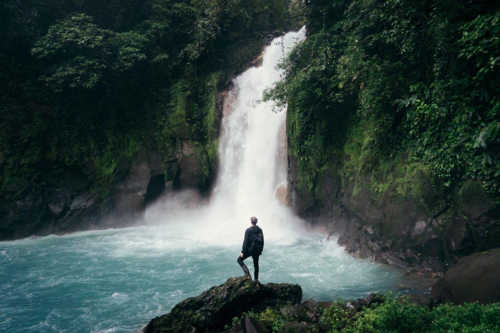 homme devant une cascade